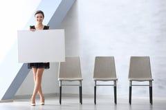 Junge Frau mit leerem Werbungsbrett stockbild