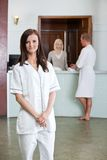 Junge Frau mit Leuten im Hintergrund am Badekurort Stockfotos