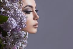 Junge Frau mit lila Blumen Stockfotos
