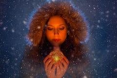 Junge Frau mit magischem Licht in den Händen nachts während eines Schneesturmes Stockbilder