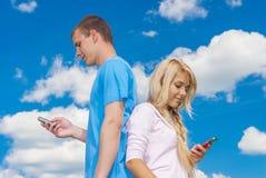 Junge Frau mit Mannlesungs-sms Stockbild