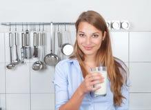 Junge Frau mit Milchshaken in ihrer Küche Lizenzfreies Stockfoto