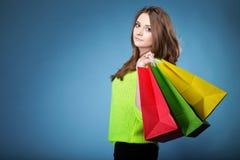 Junge Frau mit multi farbigen Einkaufstasche- oder Weihnachtspapiergeschenken Stockfotografie