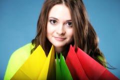 Junge Frau mit multi farbiger PapierEinkaufstasche Stockfotos
