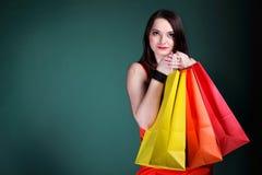 Junge Frau mit multi farbiger PapierEinkaufstasche Lizenzfreie Stockfotografie