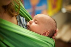Junge Frau mit neugeborenes Kinderbaby in einem Riemen mit einem unscharfen Hintergrund zu Hause stockfoto