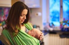 Junge Frau mit neugeborenes Kinderbaby in einem Riemen mit einem unscharfen Hintergrund zu Hause lizenzfreie stockfotografie