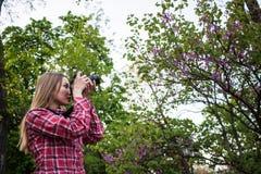 Junge Frau mit Park DSLR-Kamera im Frühjahr Lizenzfreie Stockfotos