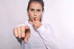 Junge Frau mit Pfeife zeigend auf Kamera Lizenzfreie Stockfotos