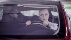 Junge Frau mit Pferdeschwanz sitzt im roten Auto, rüttelt Kopf hinter Lenkrad stock video