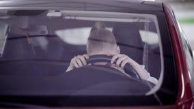 Junge Frau mit Pferdeschwanz sitzt im roten Auto und setzt Kopf auf Lenkrad stock video footage