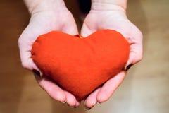 Junge Frau mit rotem Herzen in der Hand Stockfotos