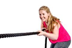 Junge Frau mit rotem T-Shirt zieht auf ein Seil Stockfotografie