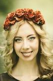 Junge Frau mit roten Blumen im Haar Lizenzfreie Stockbilder