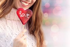 Junge Frau mit roter saugender Süßigkeit des Herzens stockfotos
