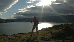 Junge Frau mit Rucksack gehend ringsum Berge und See stock video