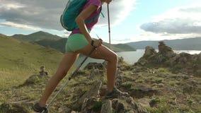 Junge Frau mit Rucksack gehend ringsum Berge und See stock footage
