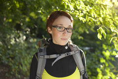 Junge Frau mit Rucksack in Holz Wandern an der Sommerzeit Stockbild
