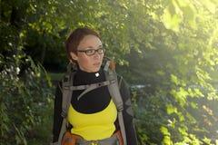Junge Frau mit Rucksack in Holz Wandern an der Sommerzeit Lizenzfreies Stockfoto