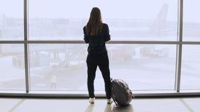 Junge Frau mit Rucksack nahe Terminalfenster Kaukasischer weiblicher Tourist, der Smartphone im Flughafenaufenthaltsraum verwende Stockfotografie