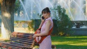 Junge Frau mit schlafendem Baby im Riemen beantwortet Telefonanruf stock video