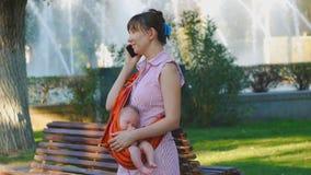 Junge Frau mit schlafendem Baby im Riemen beginnt Telefonanruf stock footage