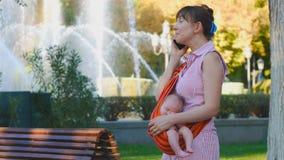 Junge Frau mit schlafendem Baby im Riemen spricht über erstaunliches Ereignis stock video footage