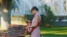 Junge Frau mit schlafendem Baby im Riemen treibt glücklich Telefongalerie Blätter stock video footage