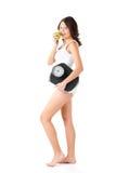 Junge Frau mit Skala unter ihrem Arm und Apfel Stockbild