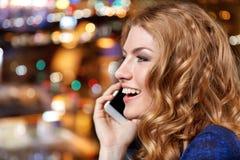Junge Frau mit Smartphone am Nachtclub oder der Bar Lizenzfreie Stockfotos