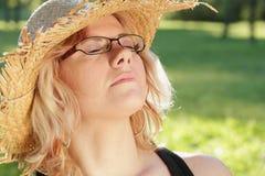 Junge Frau mit Sonnehut draußen schlafend Lizenzfreies Stockfoto