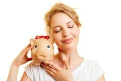 Junge Frau mit Sparschwein als Sparsamkeitskonzept Lizenzfreie Stockbilder
