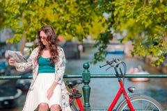 Junge Frau mit Stadtplan und Fahrräder in der europäischen Stadt Lizenzfreie Stockfotos