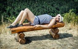 Junge Frau mit sunhat in der Seemannausstattung liegt auf dem hölzernen Lizenzfreies Stockfoto