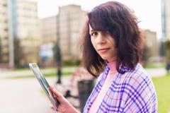 Junge Frau mit Tabletlesung Stockfotos