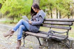 Junge Frau mit Tablette auf der Bank Stockfotografie
