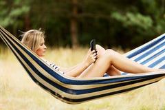 Junge Frau mit Tablette auf der Hängematte Lizenzfreies Stockfoto