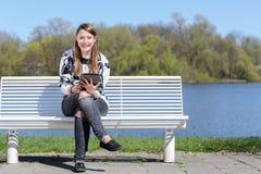 Junge Frau mit Tablette in einem Park Stockbild