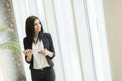 Junge Frau mit Tablette im Büro Stockbild