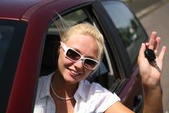Junge Frau mit Tasten im Auto Stockbilder