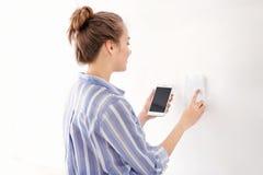 Junge Frau mit Telefon unter Verwendung des Sicherheitssystems zuhause lizenzfreie stockfotografie