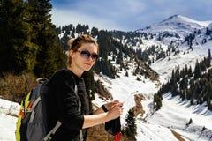 Junge Frau mit Trekking haftet in mountainsYoung Frau mit Trekkingsstöcken lizenzfreie stockfotos