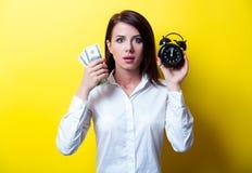 Junge Frau mit Uhr und Geld Stockbild
