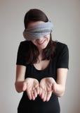 Junge Frau mit verbundenen Augen, die Palmen zeigt Stockfotografie