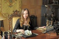 Junge Frau mit vielen Dollar in ihren Händen und in Adler auf Tabelle Lizenzfreies Stockfoto