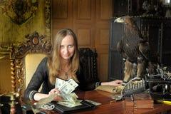 Junge Frau mit vielen Dollar in ihren Händen und in Adler auf Tabelle Lizenzfreie Stockfotografie