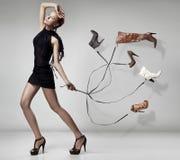 Junge Frau mit vielen Schuhen lizenzfreie stockfotografie