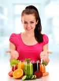 Junge Frau mit Vielzahl des Gemüses und der Fruchtsäfte Lizenzfreie Stockfotos