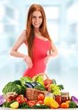 Junge Frau mit Vielzahl des organischen Gemüses und der Früchte Lizenzfreie Stockfotos