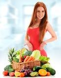 Junge Frau mit Vielzahl des organischen Gemüses und der Früchte Stockfotografie
